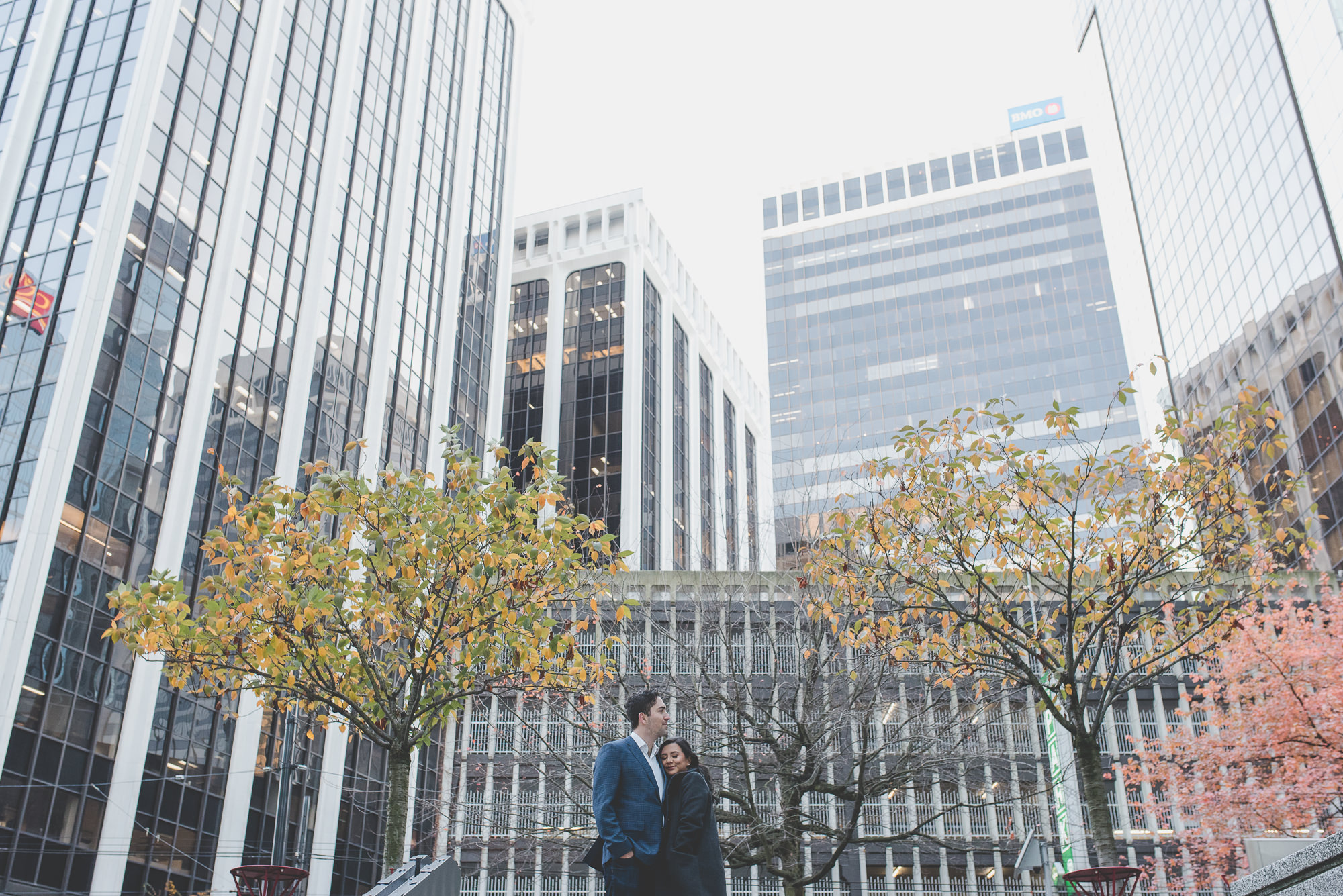 couple standing under autumn trees at Oceanic Plaza in downtown Vancouver engagement session