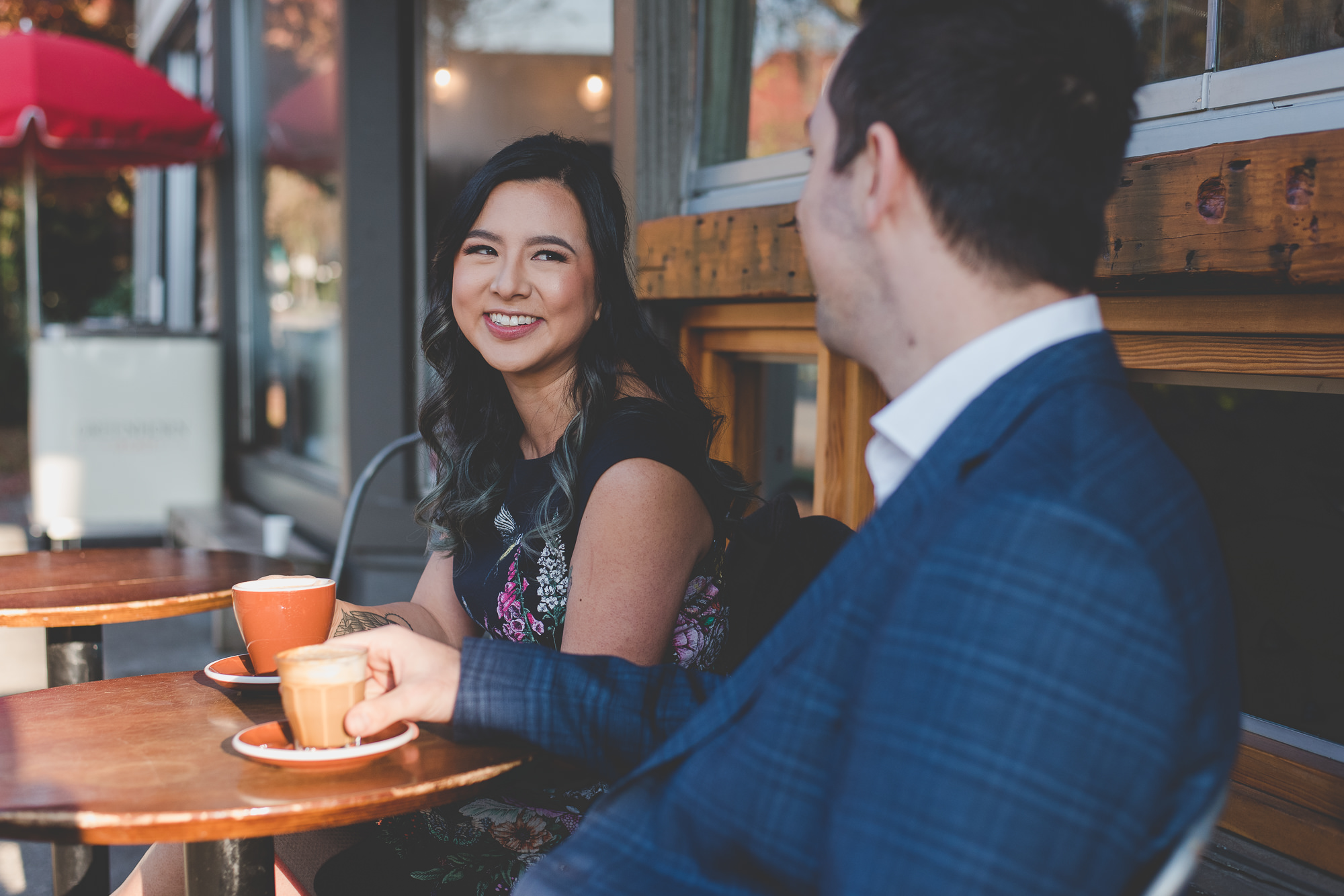 woman smiling at her partner while drinking coffee in downtown Vancouver
