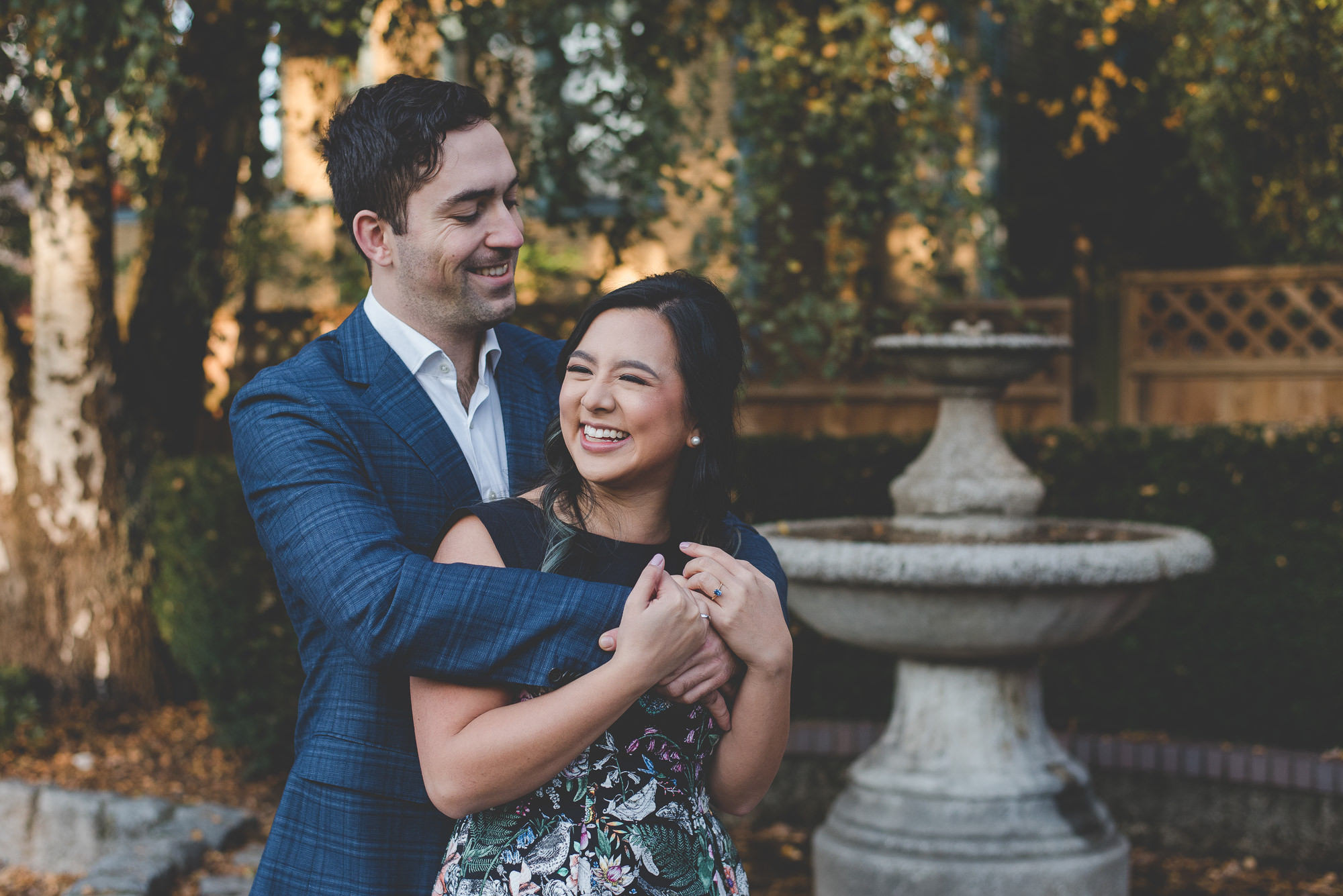 woman laughing with her fiance's arms around her shoulders in front of fountain at Barclay Heritage Square