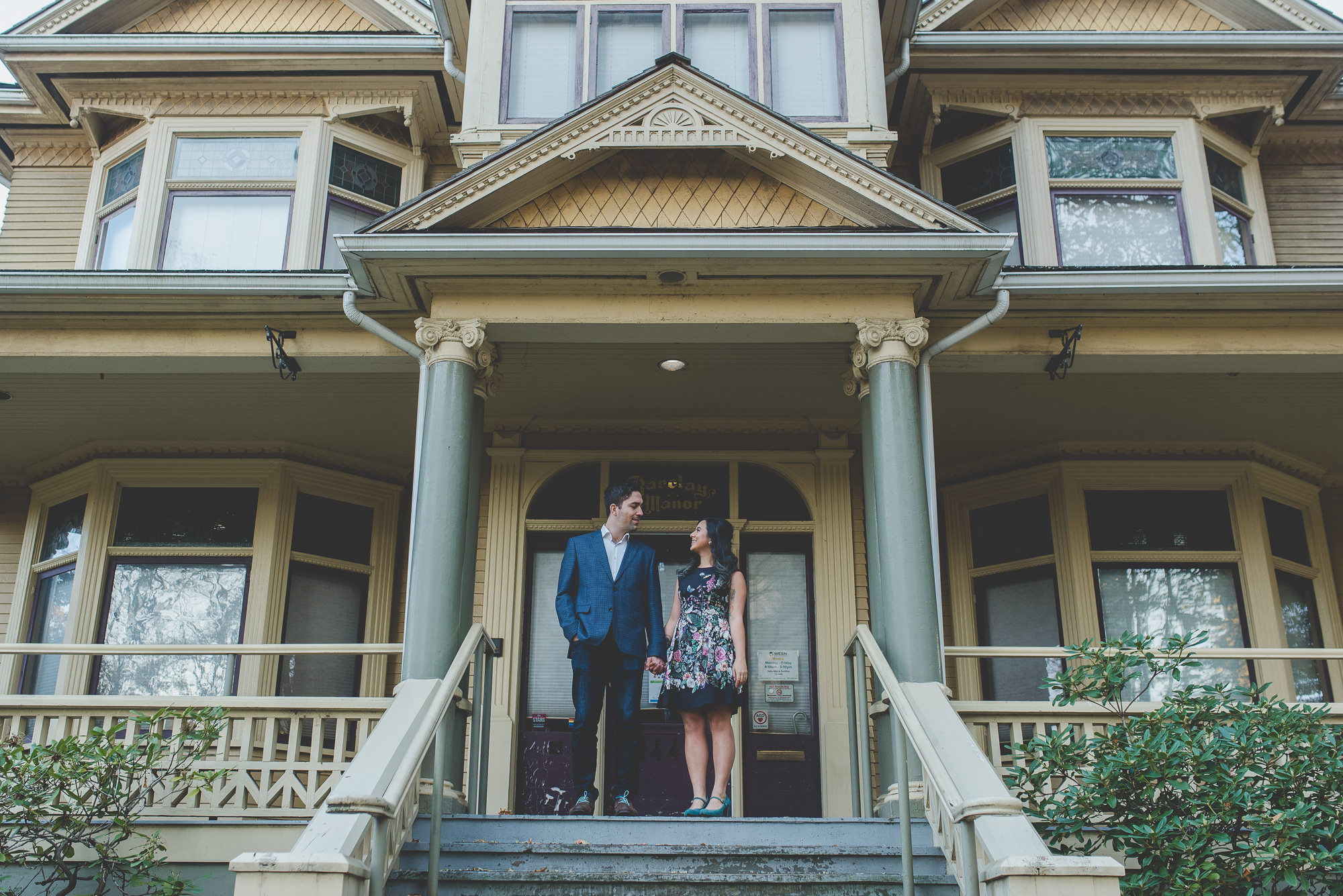 couple standing on steps of Barclay Manor and looking at eachother