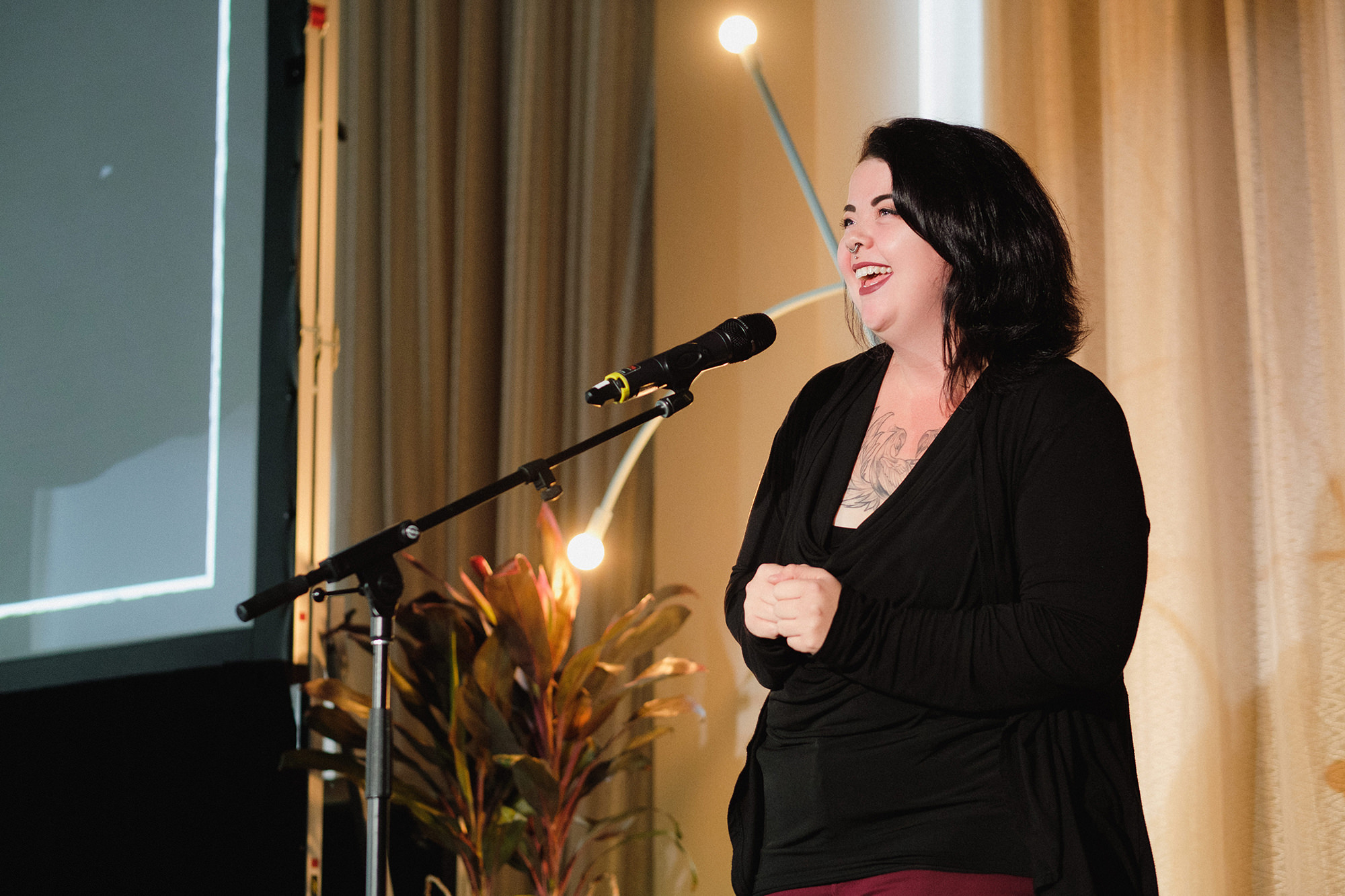 a woman wearing a black shirt and red pants standing on a stage and speaking into a microphone