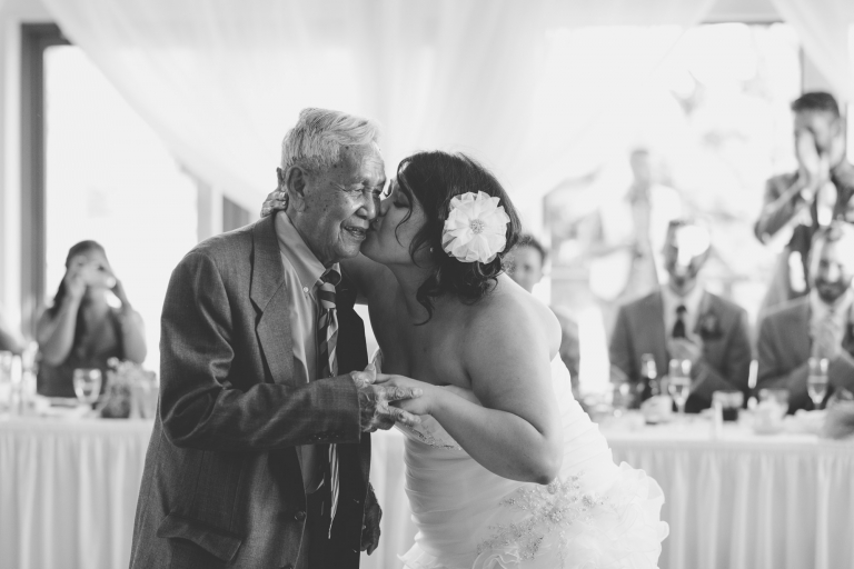bride kissing elderly grandfather on cheek after father daughter dance